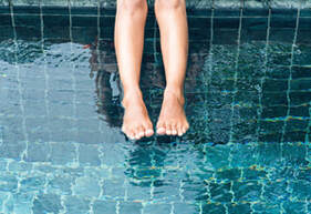 Woman hanging her legs over a green and dark blue tile pool.